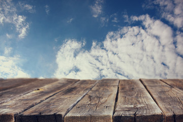 rustic wood board in front of sky with clouds