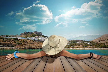 girl with straw hat rear view in lindos island