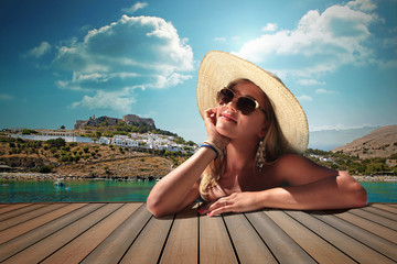girl with sunglasse and straw hat at the sea