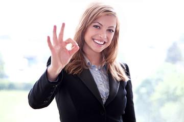 Junge blonde Frau zeigt OK Zeichen und lächelt