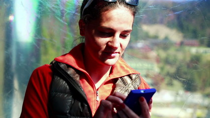 young woman using her cellphone and travelling in a cable car
