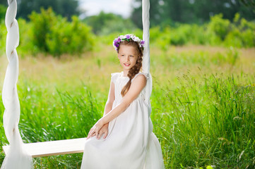 Girl in white dress sitting on a swing