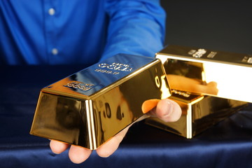 Businessman holds at hands gold brick