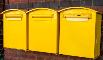 Three yellow mail-boxes