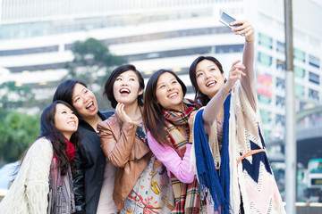 Young female friend taking selfie in Hong Kong