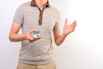 家の模型を持っているポロシャツの男性