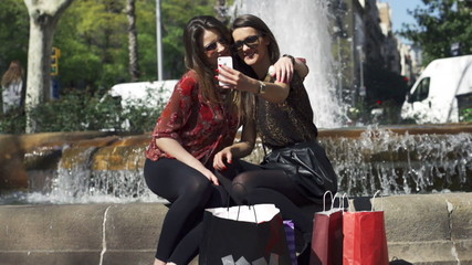 Women taking selfie and sitting on fountain, slow motion shot at