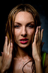 Wet girl on which water flows in a white cloth