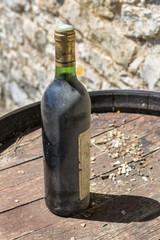 Vieille bouteille de vin rouge sur tonneau