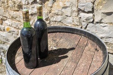 Deux vieilles bouteilles de vin rouge sur tonneau