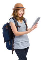 Woman using tablet with backpack