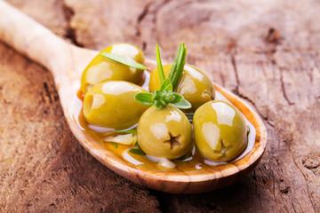 Grüne Oliven auf Holzlöffel