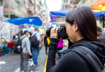 Female tourist taking photo with camera in street at Hong Kong