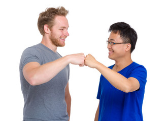 Two arm fist punch each other for caucasian and asian man