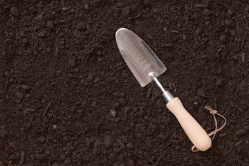 Small garden trowel lying on rich brown earth