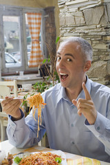 Young man enjoying spaghetti.