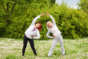 Two senior women doing stretching exercise