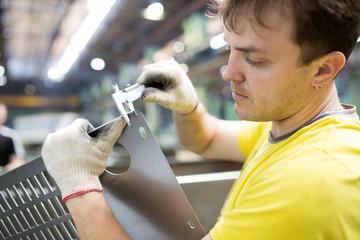 Worker Measuring Detail with Vernier Caliper in Factory Workshop