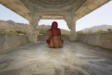 Mujer meditando en templo- India
