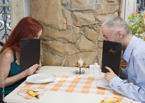 What to eat / Young couple peeking over the menu. - 65355901
