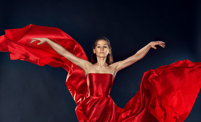 beautiful inspirational woman dancing in a red silk dress flying