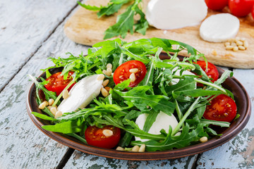 arugula salad with mozzarella cheese and cherry tomatoes