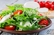 arugula salad with mozzarella cheese and cherry tomatoes