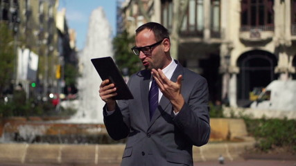 angry businessman with tablet standing in the street, slow motio