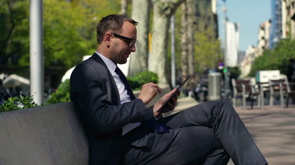 businessman working on a tablet and sitting on a bench in the st