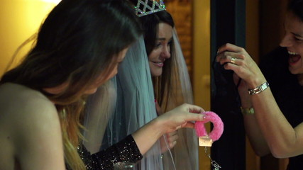 young woman opening gift at the bachelorette party, slow motion