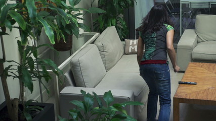 Woman jumping on the sofa in house, slow motion shot at 120fps,