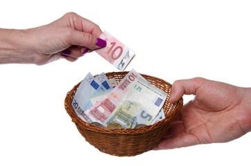 Hand putting a banknote in a basket