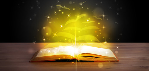 Open book with golden glow flying paper pages