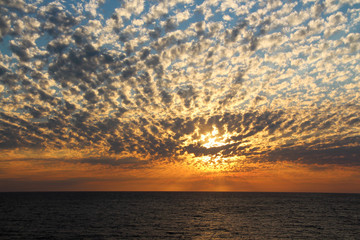 Dramatic cumulus clouds at sunset over the ocean