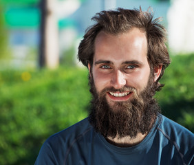 Portrait of happy bearded man on a greeen park background