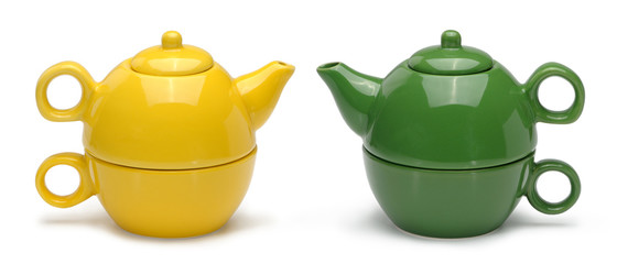 Sets of yellow and green ceramic teapots and mugs isolated on a