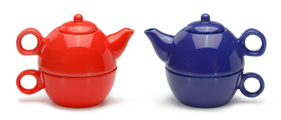 Sets of blue and red ceramic teapots and mugs isolated on a whit