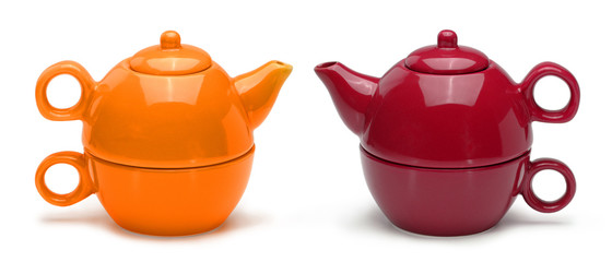 Sets of orange and red ceramic teapots and mugs isolated on a wh