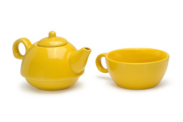 Set of a yellow ceramic teapot and mug isolated on a white backg