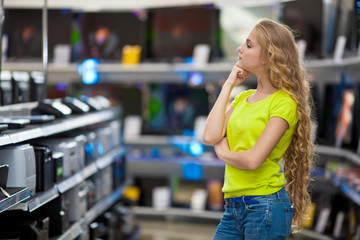 Девушка выбирает технику в магазине