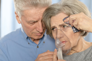 Elderly couple with inhaler