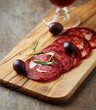 Chorizo Sausage with Olives on a Wooden Chopping Board