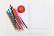 Цветные карандаши, тетради и яблоко на белом фоне