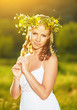 beautiful woman in wreath of flowers  in the green grass outdoor