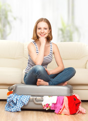 happy woman is packing suitcase at home