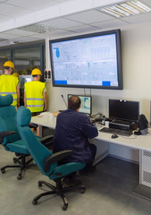 Workers in thermal plant's control room.