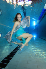 Woman with dress posing underwater in the pool