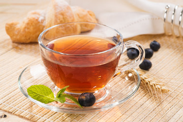 Cup of black tea with mint and fresh berries blueberry