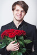 Young handsome man dressed in a black suit with a red roses