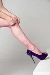 Woman adjusting red fishnet tights